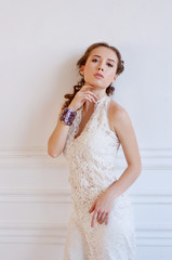 Tender young bride with curly brown hair, white gown and beaded
