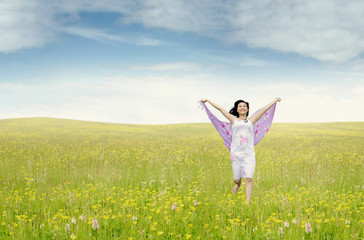 Pretty woman with fabric running on meadow