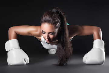 beautiful sexy kickboxer girl dressed in gloves and push up;