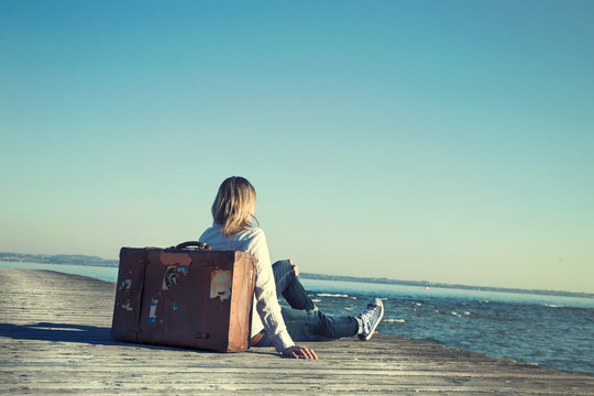 woman sitting on her suitcase waiting for the sunset in a specta