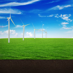 Windmill green energy on a beautiful landscape of green grass, the soil and the sky with clouds
