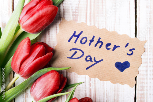 Mother's Day card and a bouquet of beautiful tulips on wooden background