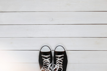 Black sneakers with laces on a white wooden floor. top view