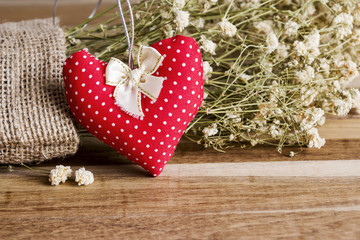 Heart fabric and dry flowers on wooden background
