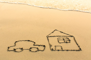 Car and a house drawn on the sand beach with the soft wave.