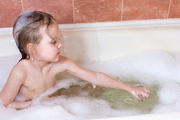 little girl taking bath with foam