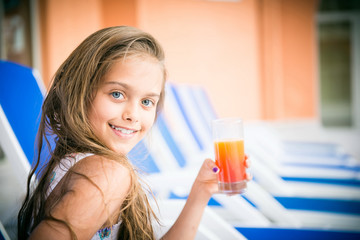 girl drinking juice on a deck chair. beautiful girl with a glass of juice. vitamin deficiency and healthy food for children