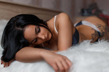 Young beautiful sexy girl in lingerie sleeping on a bed