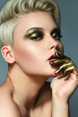Portrait of a girl with short white hair. On the face makeup antique gold. Looking into the camera. Fingers painted in gold paint.