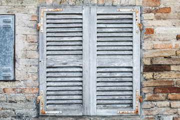 Old window with white closed wooden shutters