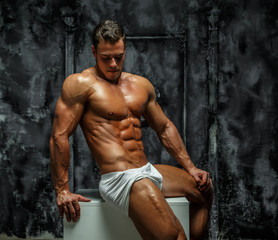Shirtless bodybuilder in a white pants.
