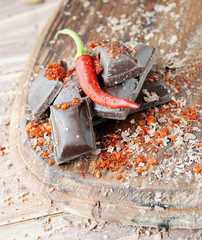pieces of chocolate with chili peppers on a wooden table