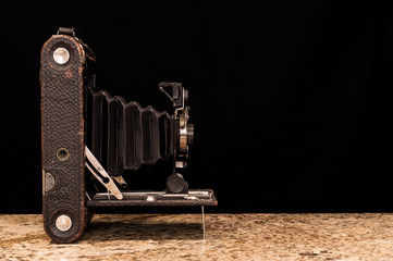 Antique film camera with bellows on black background