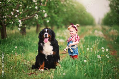baby girl with dog bern in spring garden