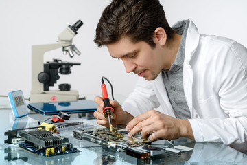 Young energetic male tech or engineer repairs electronic equipme
