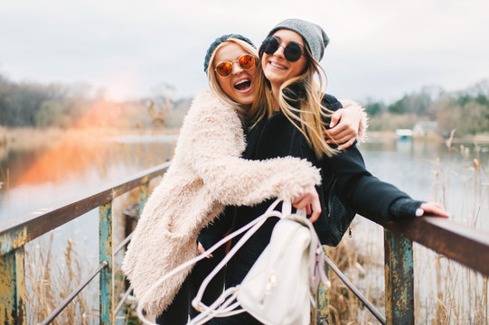 Outdoor lifestyle portrait of two best friends, smiling and having fun together, enjoy each other company posing and making selfie pictures to each other and share happiness