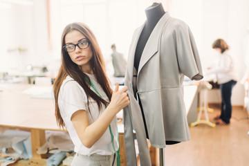 Young female fashion designer working on garment on dressmaker's model