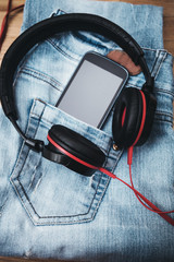 headphones smat phone and blue jeans