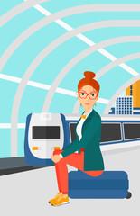 Woman sitting on railway platform.