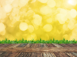 Empty wooden deck table and grass with gold glitter sparkle defocused rays lights bokeh abstract background. Product display template