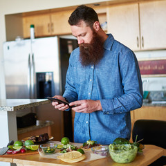 bearded man following recipe on tablet to make street tacos