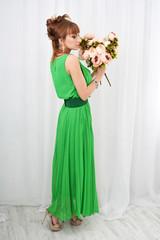 Красивая сексуальная привлекательная девушка в зеленом платье и  букетом цветов в руке позирует в белой комнате (фотостудии)