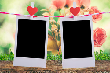 2 Blank instant photo and red clippaper heart hanging on the clothesline with wooden table floor and pink rose flower background. vintage tone.Designer concept.
