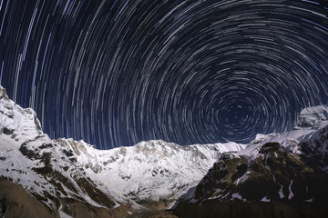 Uroboros. Star-trails over the snowy mountain peaks. Nepal, Annapurna region, Annapurna I from the Annapurna Base Camp.