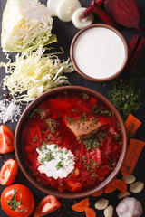 Ukrainian red soup borsch with ingredients on slate closeup. vertical top view