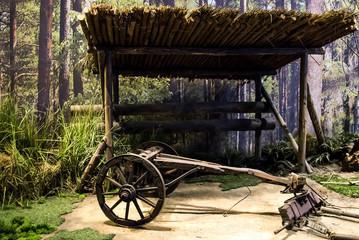 Old wooden coach wheel near barn in the village