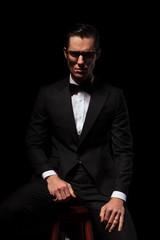 smart businessman in black posing in dark studio wearing glasses