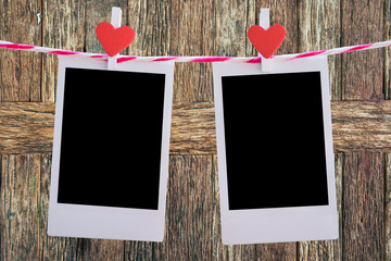2 Blank instant photo and red clip paper heart hanging on the clothesline with old wood background.Designer concept.
