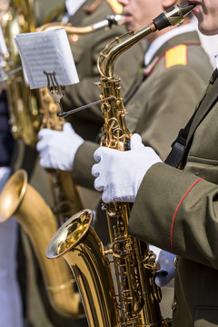 military brass band musicians plays saxophones on parade