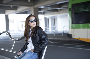 Young woman wearing a leather jacket is waiting for the bus