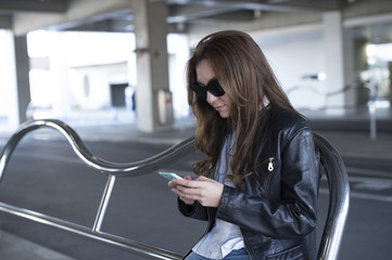 Young woman wearing a leather jacket and sunglasses are using a smart phone outside