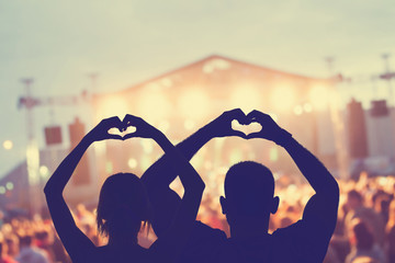 Couple enjoying the concert together while holding a heart-shape symbol with their hands.