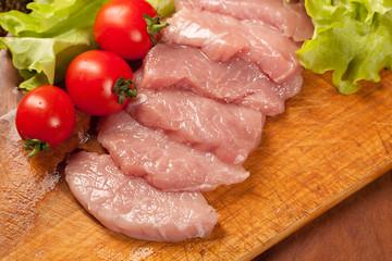 Raw pork оn the wood board. Tomato and lettice