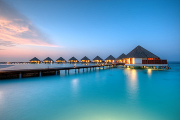 Water villas on Maldives resort island in sunset