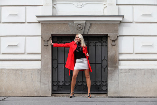 Sexy blonde woman wearing red coat and mini skirt on the street
