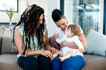 Lesbian couple playing with their baby