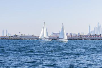 background seascape two sailboat met in the Gulf opposite the Dubai Marina in Dubai