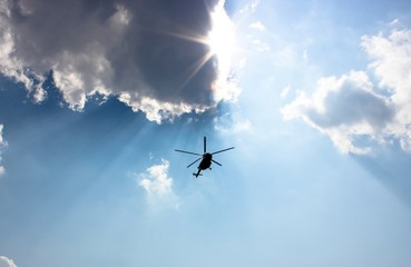 Helicopter flying in the sky among the rays of the sun