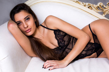 Beautiful young girl in sexy black lingerie on a bed