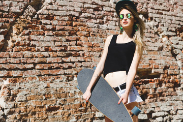 Young blond woman posing with skateboard on the street