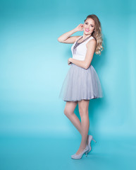 Full body portrait of young attractive blonde smiling woman wearing dress and high heels over a blue background