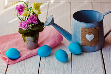 Easter background with blue Easter eggs and watering can on white wooden background