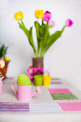 Colored speckled egg in a small pink watering pot