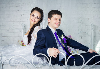 Attractive smiling happy bride and groom in ceremonial clothing sitting on a bed