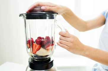 close up of woman with blender making fruit shake