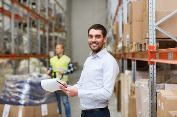 happy businessman with clipboard at warehouse